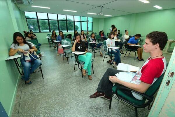 Pessoas fazendo a prova do vestibular da UNEB