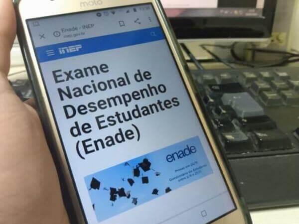 Pessoa segurando smartphone com página do Enade em aberto