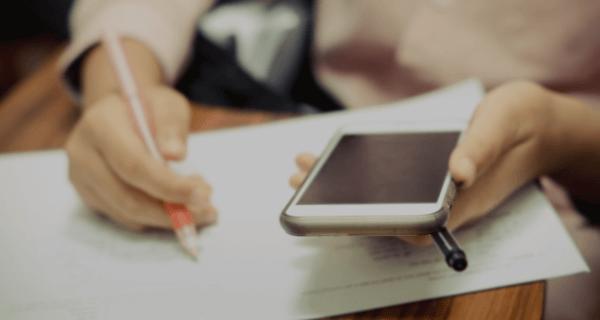 Pessoas utilizando celular e provas impressas para estudar para Educa Mais Brasil